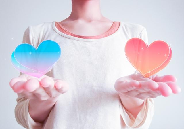 ブルーとピンクのハートを手にのせる女性