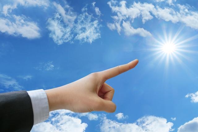 太陽に向かって指を指す