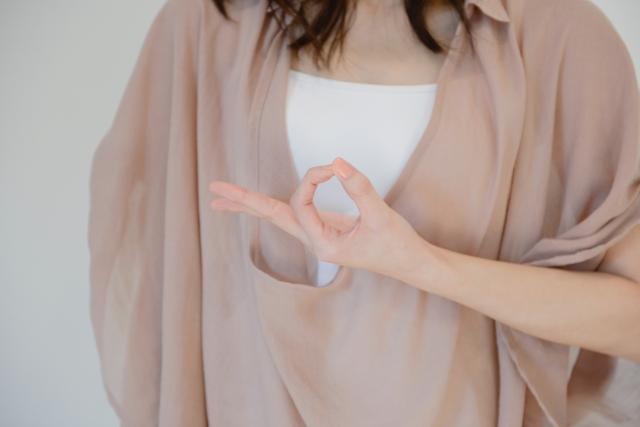 指でOKポーズを作る女性