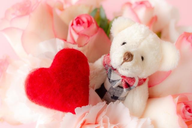 花の中のクマの人形とハート