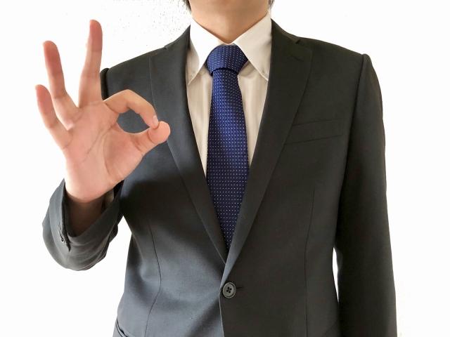 指でOKポーズをする男性