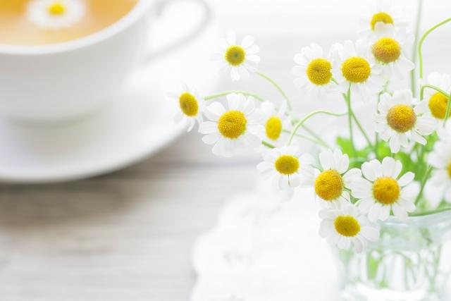 テーブルの上のカフェラテと花