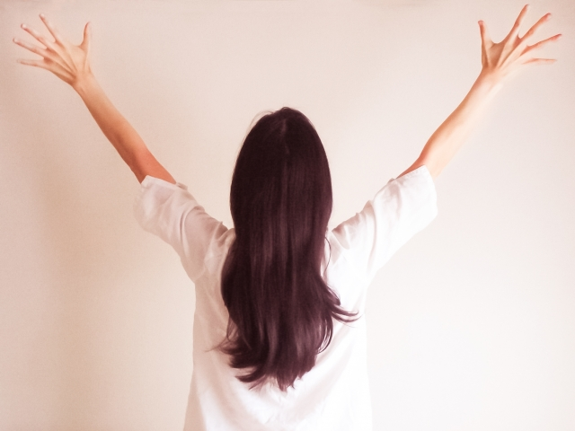両手を上に広げる女性