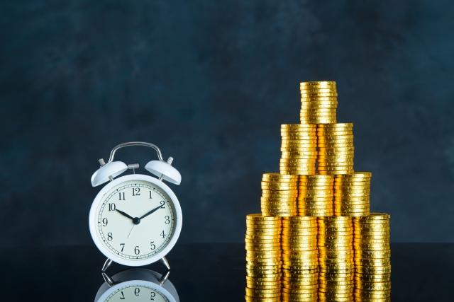目覚まし時計とコインの山