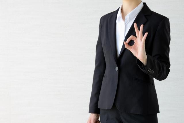 指でOKポーズをとる女性