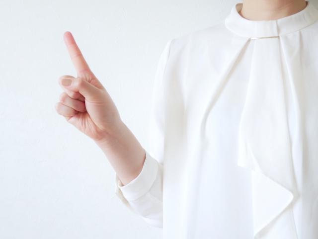 指を指すポーズをとる女性
