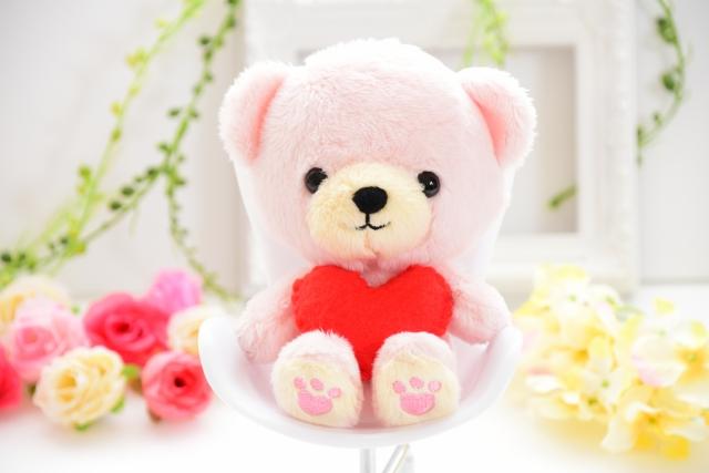 花に囲まれたハートを持ったクマの人形