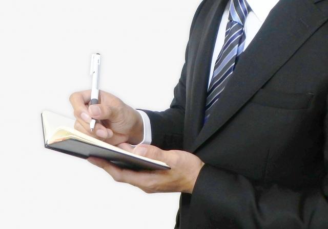手帳に予定を書き込む男性