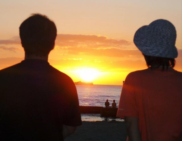 黄昏時に海を見る男女