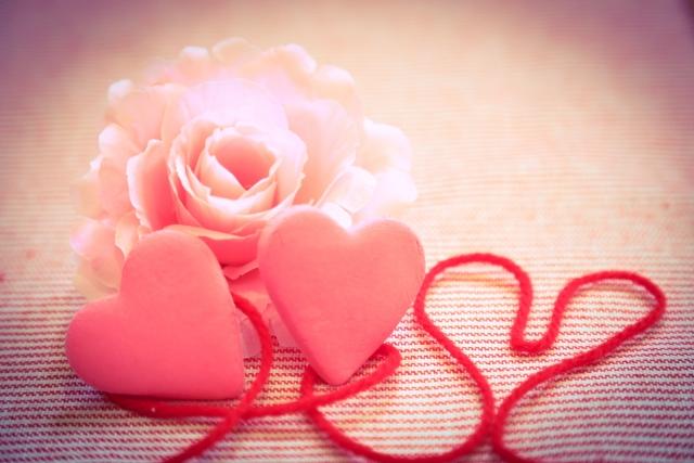 ピンクのバラの花と2つのハートと赤い糸