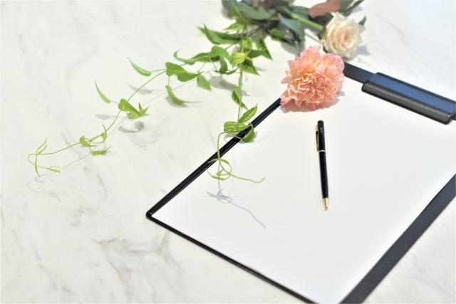バインダーに挟まれた大きなメモ用紙とペンと花