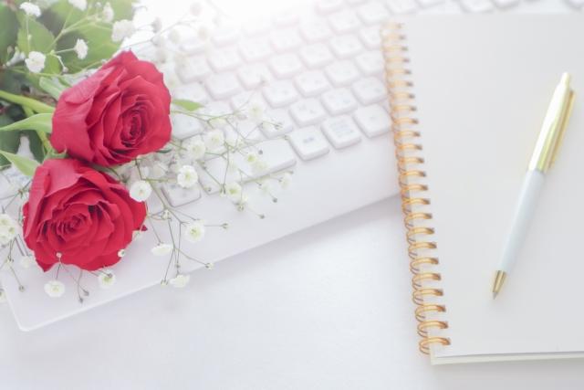 ノートとキーボードとバラの花