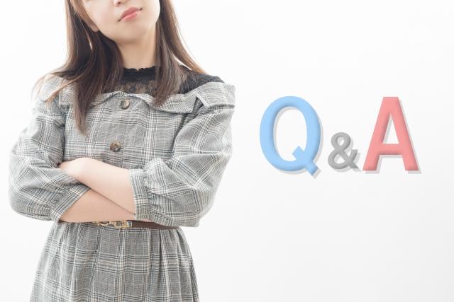 Q&Aの文字と腕を組んで考える女性