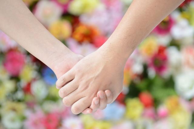 たくさんの花の前で手を繋ぐ男女