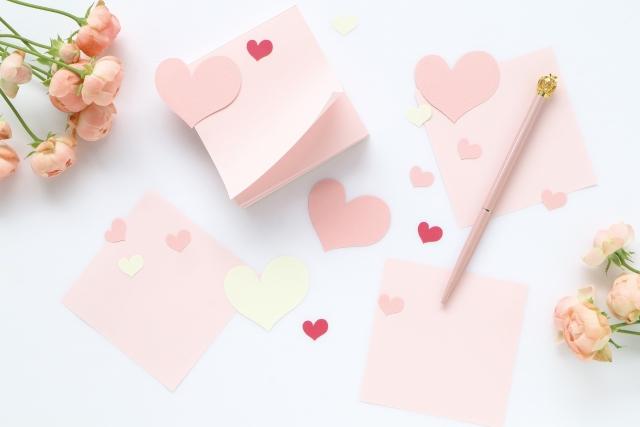ピンクのメモ用紙とペンと花