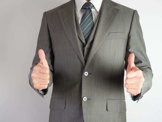 両手の親指をたてるポーズをとる男性