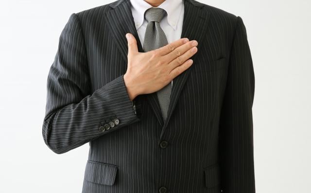 胸をおさえるスーツの男性