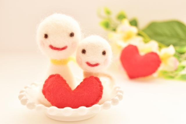 毛糸で作られたカップルの人形とハート