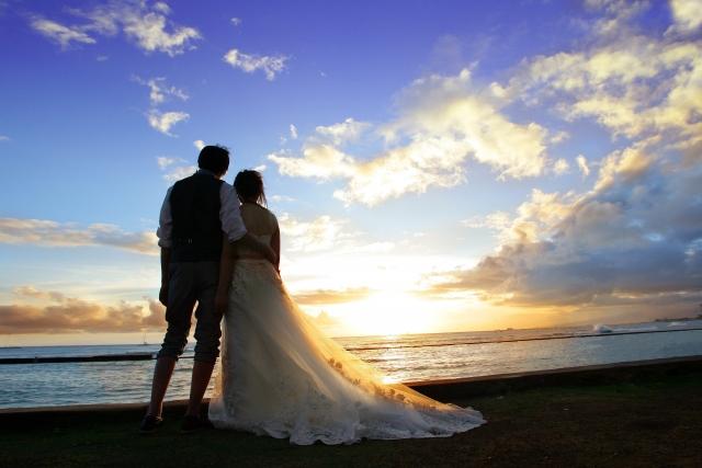 海岸で夕日に向かって寄り添う新郎新婦