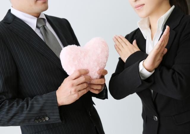 ハートを持つ男性に対してバツのポーズをとる女性